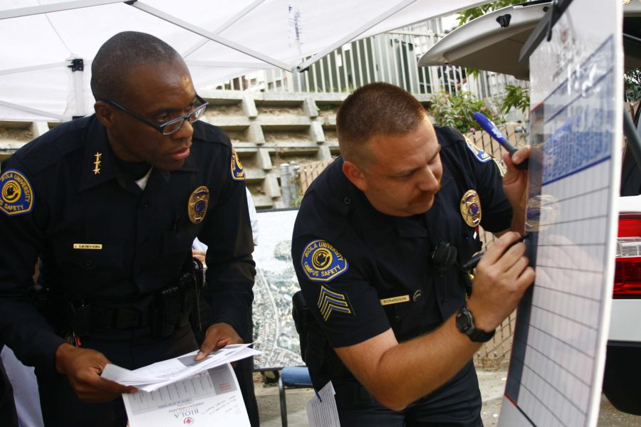 Deputy Chief John Ojeisekhoba and Sergeant Randy Richardson mark the information board during the disaster simulation drill on Friday. Many students received a text message to test the effectiveness of the 3N System that Campus Safety implemented this year. Photo by Faith Martinez