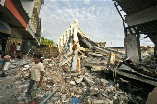 An Indonesian girl walks near the rubble of a building flattened by earthquake in Padang, West Sumatra, Indonesia, Wednesday, Oct. 7. A 7.6 magnitude temblor devastated a stretch of more than 60 miles along the western coast of Sumatra island on Wednesday. (AP Photo/Dita Alangkara)