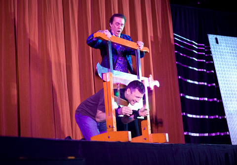 Erik Thoennes under the guillotine during André Koles performance Friday night in Sutherland Auditorium. The show was a fundraisier benefiting the California School Project, a group that evangelizes at high schools around Southern California. | BETH CISSEL / The Chimes