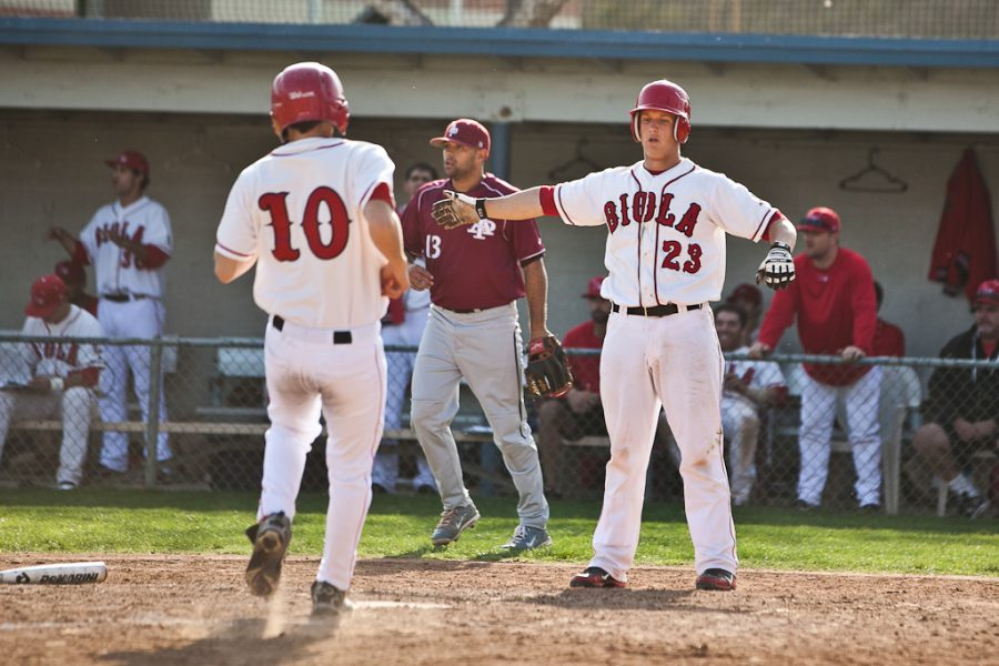 Sophomore+Javier+Martinez+is+greeted+at+home+plate+by+senior+Nick+Covyeau.+The+Eagles+split+a+doubleheader+with+Azusa+Pacific+on+Saturday%2C+Feb.+25.+%7C+Job+Ang%2FTHE+CHIMES