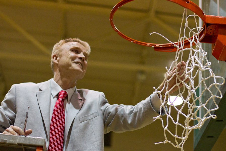 Men's basketball coach, David Holmquist, cuts down the basketball net at Concordia University in celebration of the winning the GSAC Tournament Championship on March 6, 2012. The Biola Eagles beat the Concordia Eagles with a final score of 81-77. | Tyler Otte // THE CHIMES [file]