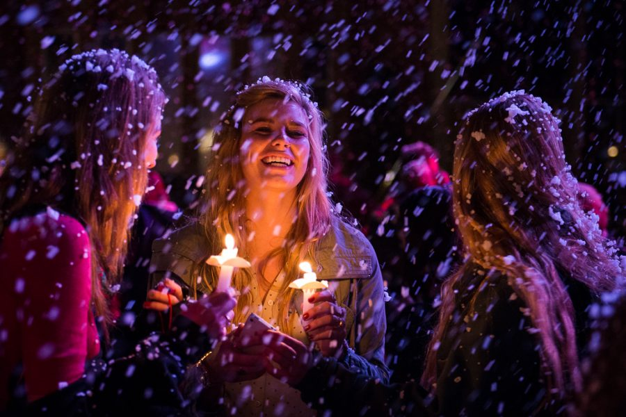 Senior Tenielle Schroeder, sophomore Rebekah Schlick, and junior Holly Emerson share a laugh underneath the freshly fallen fake snow. | Olivia Blinn/THE CHIMES