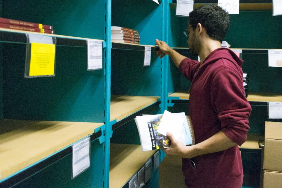 Sophomore Alex Ortiz fills a book order for a student during his shift at the Biola Bookstore. Ashleigh Fox/THE CHIMES