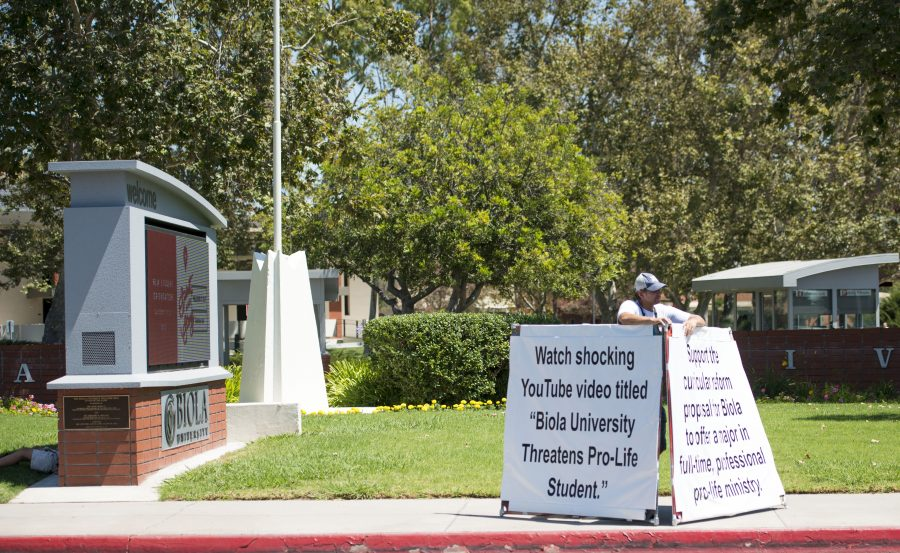 A man stands in front of the main entrance at Biola advertising a YouTube video titled,