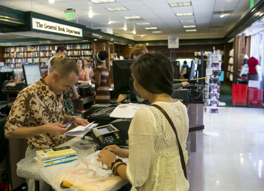 Staff member Joseph Peckham helps senior Bree Olson finish her purchases. Follett Higher Education Group now manages the campus bookstore.
