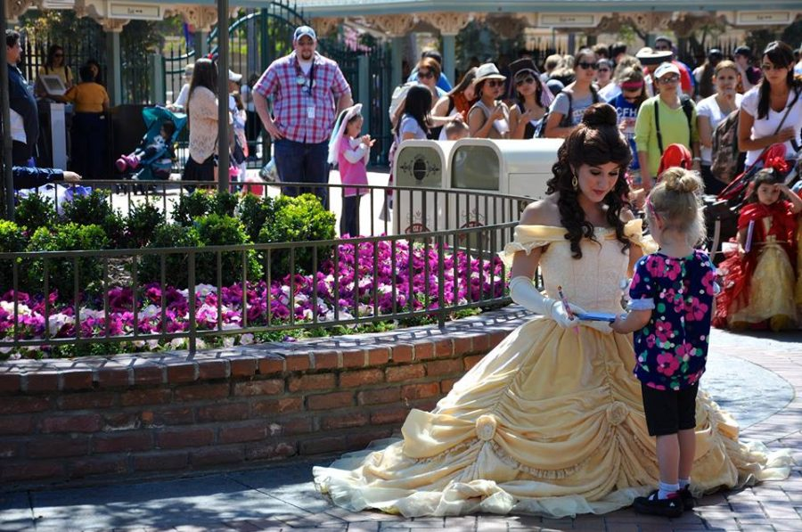 Princess Belle gives her autograph to a guest at Disneyland. Sophomore Heather Jungkeit, friends with both Belle and Sleeping Beauty, shares the extra magic that happens during Halloween.    Courtesy of Heather Jungkeit