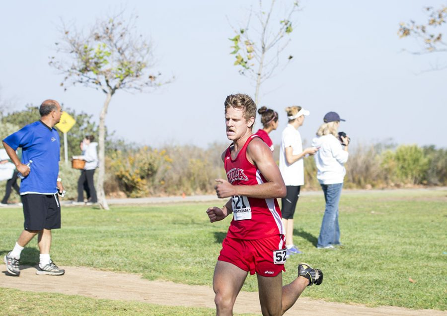 Junior Kevin Horchler exerts his last bit of energy on the final stretch of the 8K at the Vanguard Invitational on October 12. Horchler was the first to cross the finish line for the Eagles with a time of 25:21.32. | Ashleigh Fox/THE CHIMES