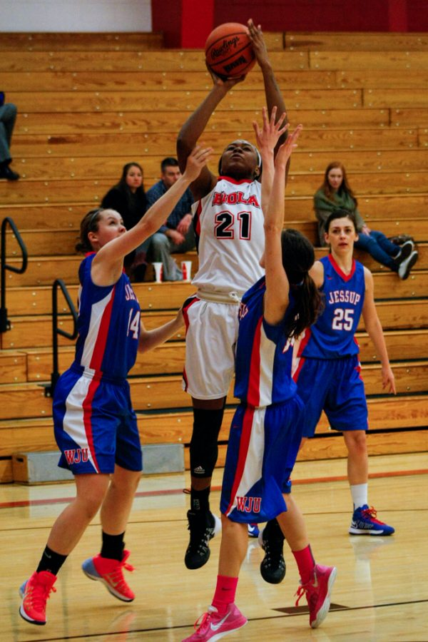 Senior Adijat Adams fights through two defenders for a jump shot during the game vs. William Jessup University on Dec. 7. Womens basketball earned their first win on Dec. 10 at home, defeating Whittier College 74-56. | Elizabeth Kay/THE CHIMES