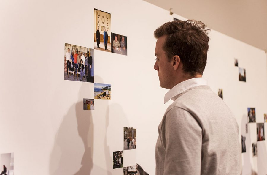 A student lingers at a piece of art featuring photos of the late Loren Baker, respectfully honoring his life during a special gallery this week. | Melanie Kim/THE CHIMES