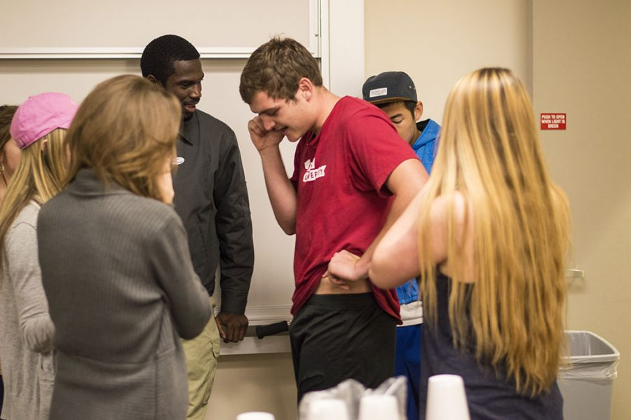 A group of friends surround SMU candidate Cody Storm, a sophomore international business major, while on the phone with current SMU president Roddy Garcia. Storm is the SMU president for the 2014-2015 school year. | Julia Henning/THE CHIMES