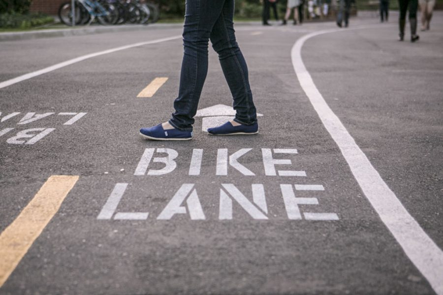 A student walks directly across the new bike lanes that run through the main part of campus. The lanes that were painted over interterm are an attempt to help with traffic flow on campus. | Melanie Kim/THE CHIMES