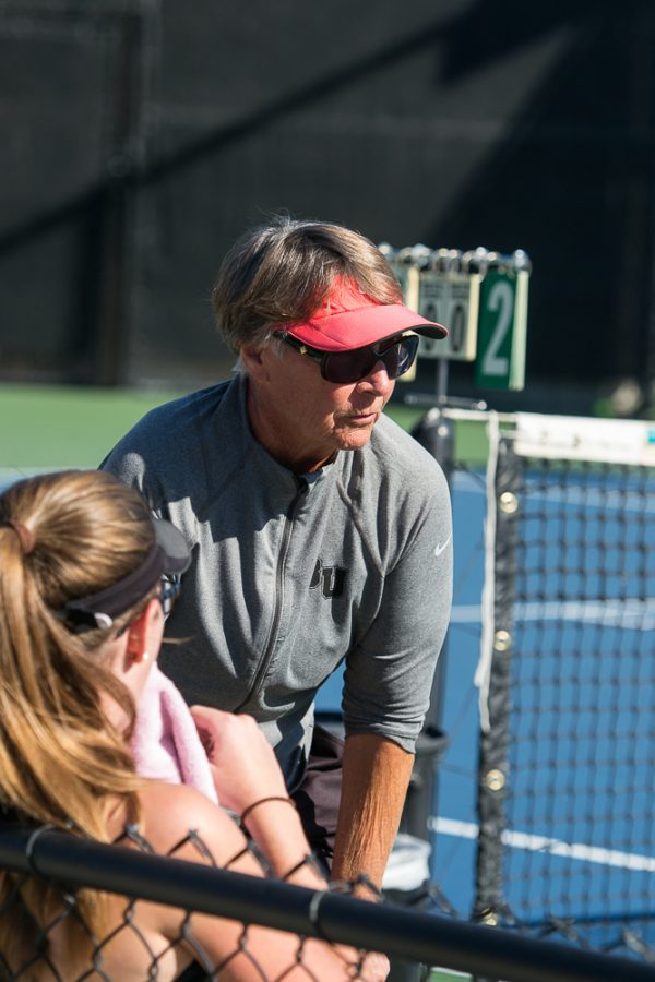 Women's tennis coach Dee Henry talks with doubles team freshman Kelsey Post and Junior Lauren Vogel between sets during Saturday's competition against Cal Tech.   Ashleigh Fox/THE CHIMES
