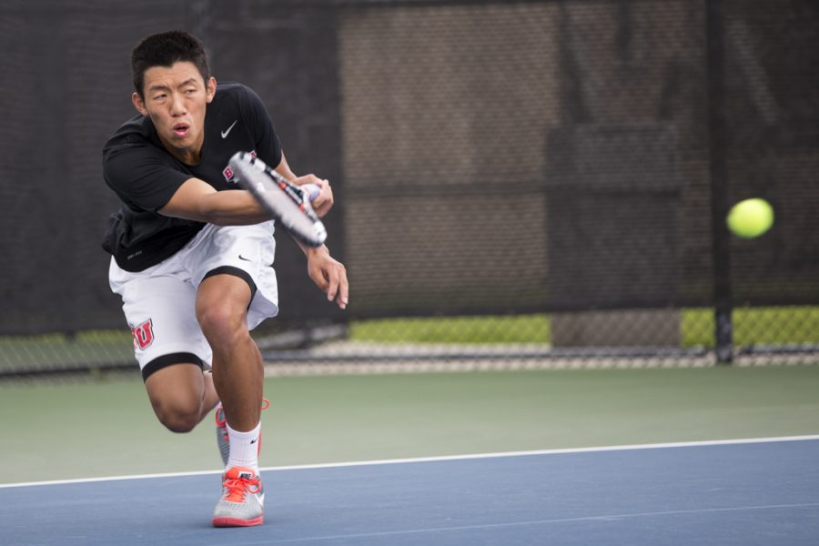 Junior Brandon Cheng pounds the ball over the net to his Hope International opponent. The mens tennis team collectively overpowered Hope International on March 25. | Amylia Lewis/THE CHIMES