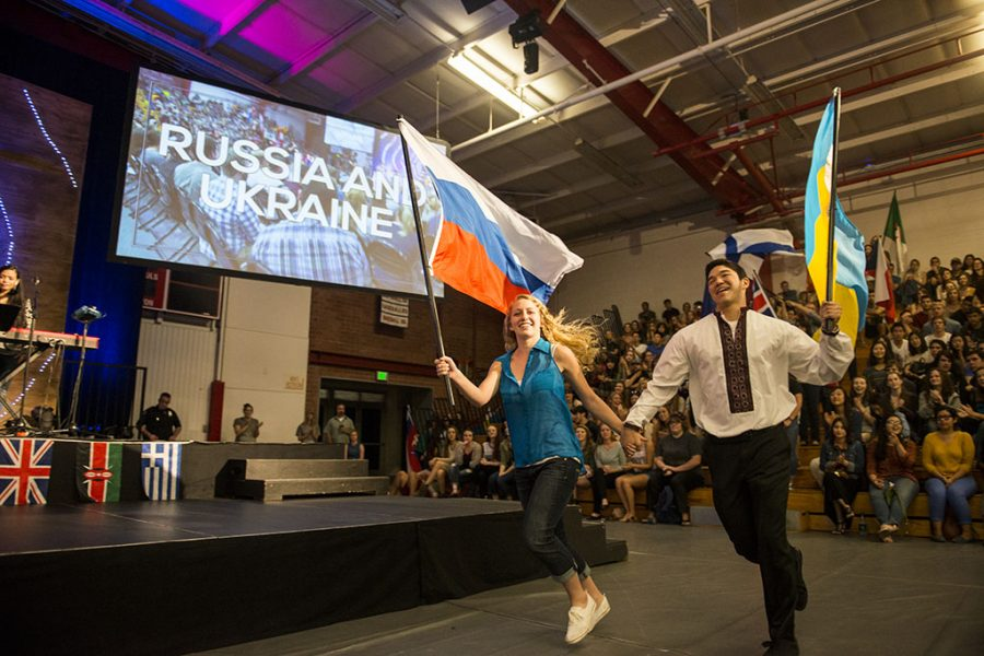 Volunteers Hannah Romick and Benjamin Saucy hold hands as they run out, flying the flags of Russia and Ukraine. | Olivia Blinn/THE CHIMES