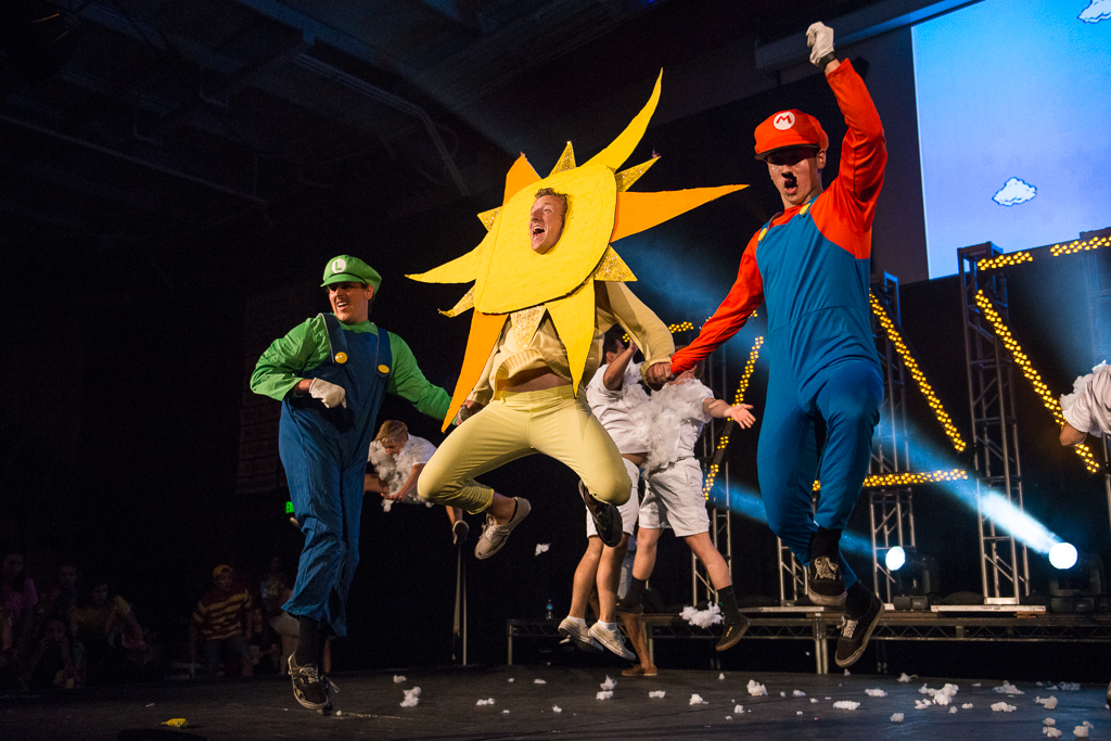 Junior Brad Winsbury, as Luigi and Sam Becker-Miyadai, as Mario jump for joy with Zach Arnold during the Bropoc performance. BroPoc comes out on top, winning first place at Mock Rock with their video game-themed dance. | Olivia Blinn/THE CHIMES