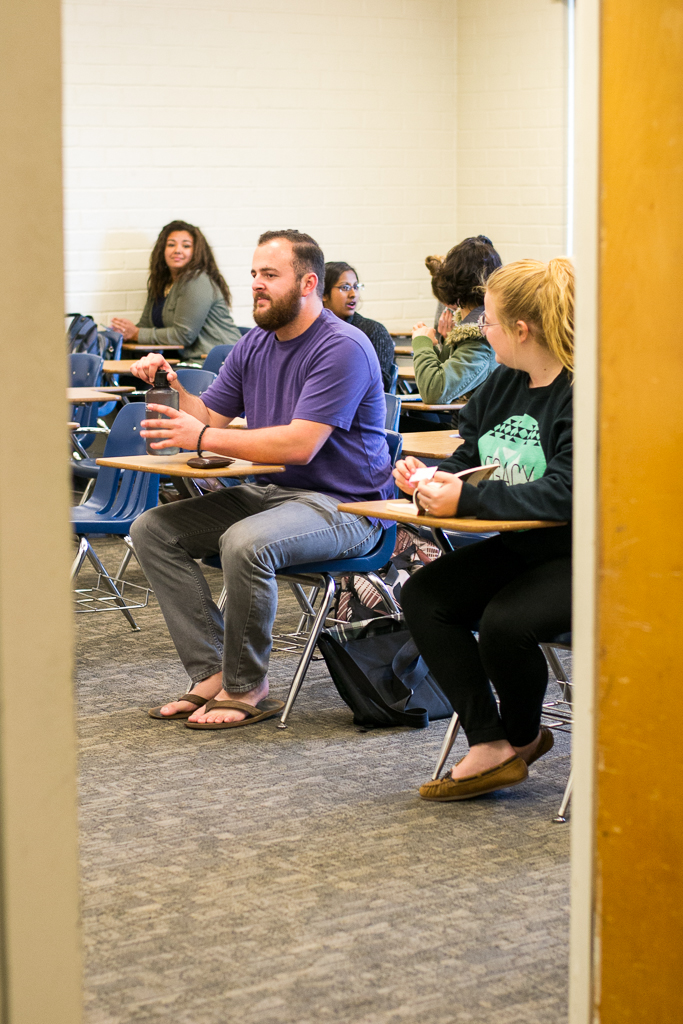 Junior Kyle Relph sits among scattered classmates and several empty desks in his ASL class. Professors like Biblical studies professor Jeff Volkmer try not to turn students away, but because of the cap, it happens often and students are put on waiting lists. | Ashleigh Fox/THE CHIMES