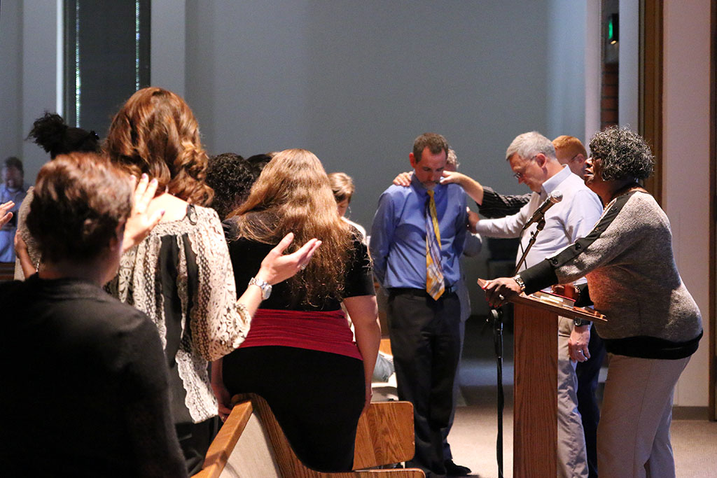 Biola staff prays over Geoff Marsh, director of financial aid, after April Jace's death was announced Tuesday afternoon. A service was held in Calvary Chapel to pray over the staff and Jace's family. | Aaron Fooks/THE CHIMES