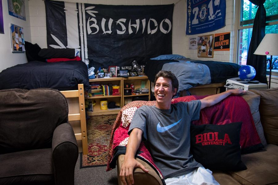 Junior Jon Blea explains the significance of the Bushido banner that covers his wall along with other decorations in his room, including the handmade pillow from his mother. | Jenny Oetzell/THE CHIMES