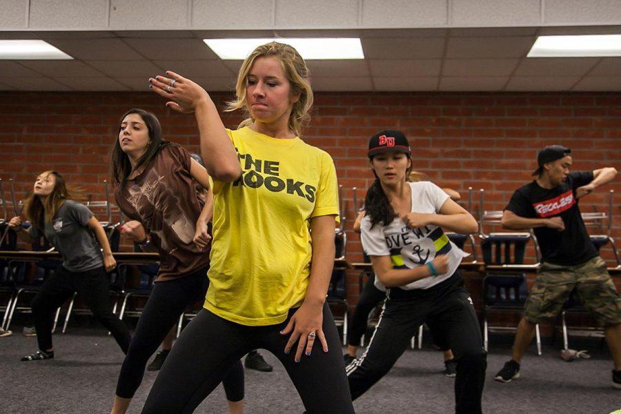 Freshman cinema and media arts major Maggie Gray dances with XOPOC members during a rehearsal. | Melanie Kim/THE CHIMES