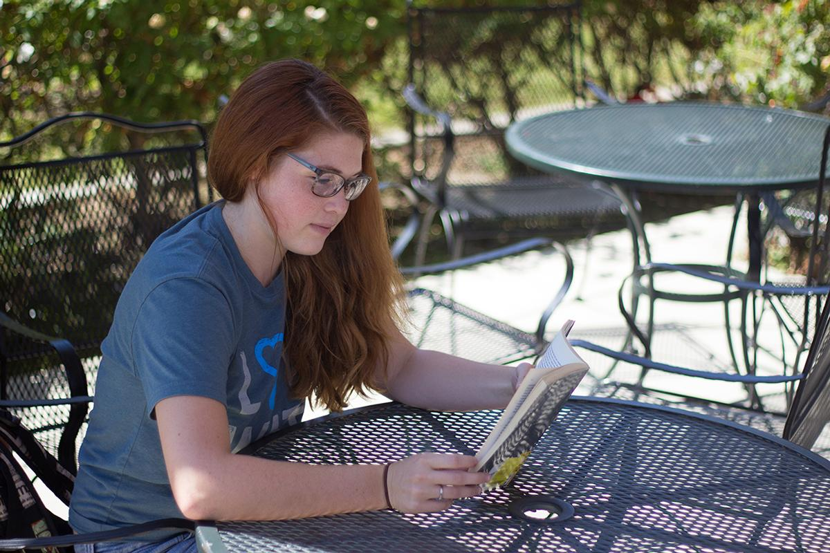Sophomore English major Grace Hansen enjoys a book at the patio near the Flour Fountain. | Johnathan Burkhardt