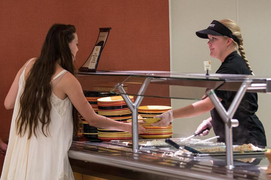 Junior Leah Woodside serves a fellow Biola student food at the Biola Café during dinnertime. | Tomber Su/THE CHIMES