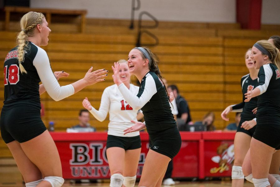 Freshman setter Allison Spencer celebrates with her teammates after the Eagles win against Hope International. The team finished their last game with a score of 25-12. | Jenny Oetzell/THE CHIMES