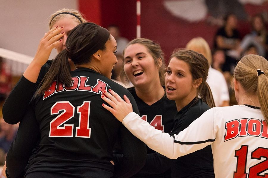 From left to right, Amy Weststeyn, Britta Blaser, Ashton Arbuthnot, and Alex Brehaut congratulate junior outside hitter Joclyn Kirton (21) on a good play at their game against The Masters College. Kirton scored 13 kills in the game on Oct. 2, helping the team to defeat the Mustangs. | Marika Adamopoulos/THE CHIMES