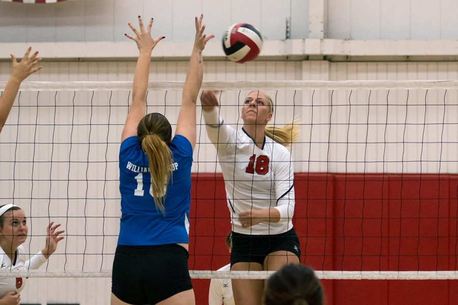 Senior middle blocker Amy Weststeyn spikes the ball down to a William Jessup University player at the game on Oct. 4. | Molli Kaptein/THE CHIMES