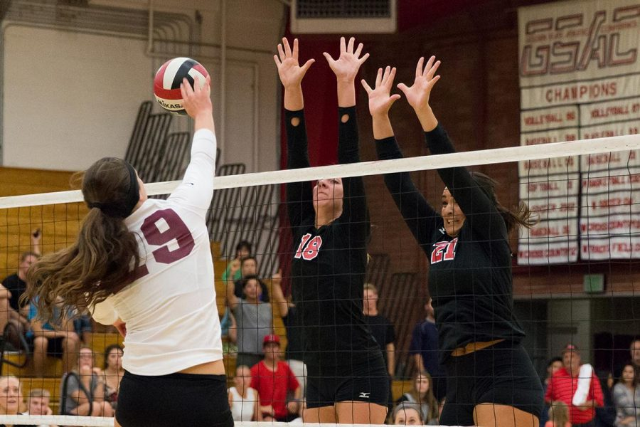 Senior middle blocker Amy Weststeyn and junior offensive hitter Joclyn Kirton jump to block a hit from Westmont College on Oct. 7. | Molli Kaptein/THE CHIMES