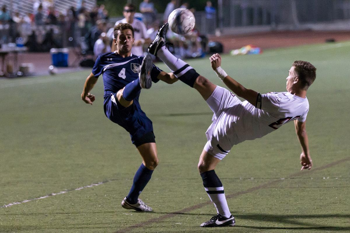 Junior midfielder Joey O'Keefe high-kicked for the ball at the game against San Diego Christian College last season. |  Johnathan Burkhardt/THE CHIMES [file photo]