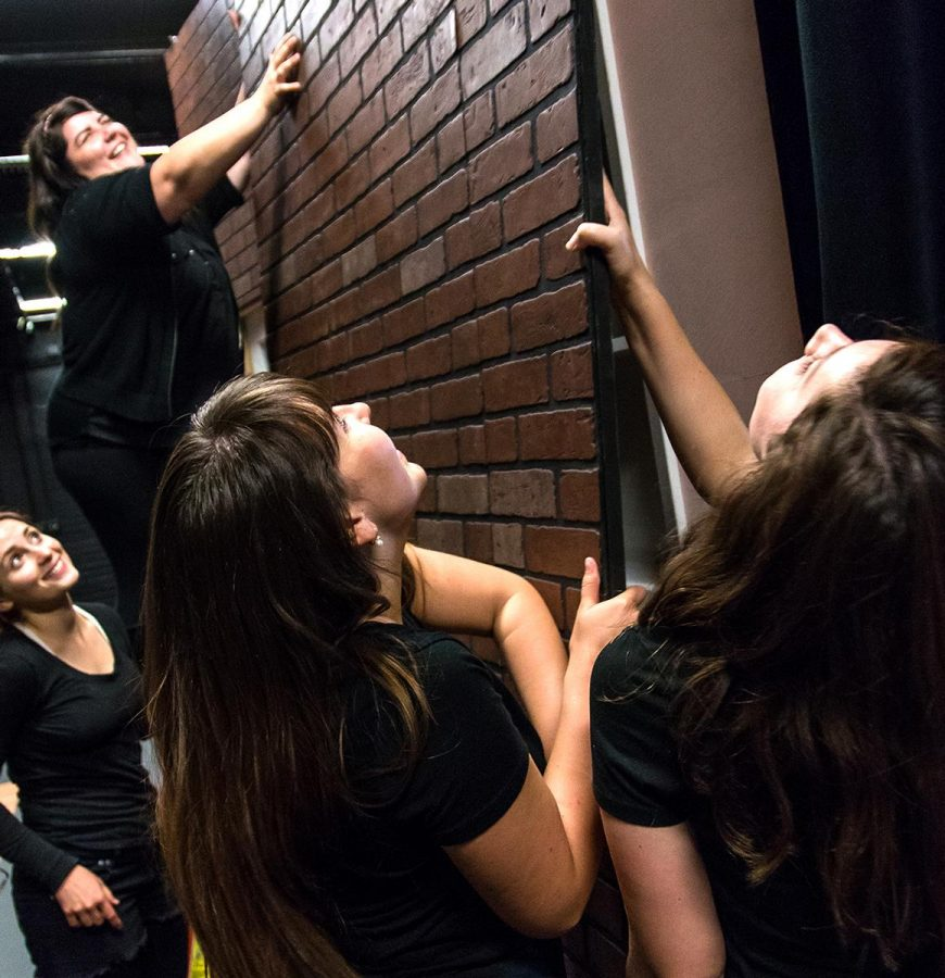 Crew members, including Alison Ross and Jenna White, pull out the reversible walls between scenes to transform the stage. From a condo to a South Carolina garden in the production of