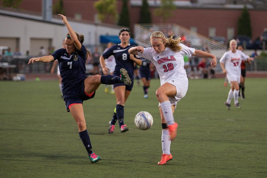 Senior Brittany Beam of San Diego Christian College shys away from a kick by sophomore midfielder Jessie Burns on Oct. 22. | Katie Evensen/THE CHIMES