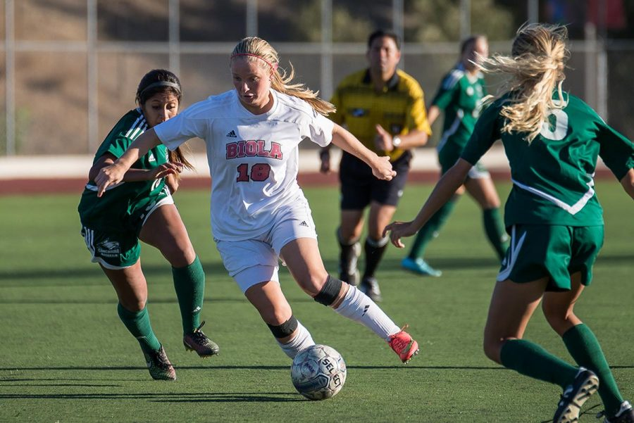 Sophomore midfielder Jessie Burns races past two players from Concordia University last season. | Jenny Oetzell/THE CHIMES [file photo]
