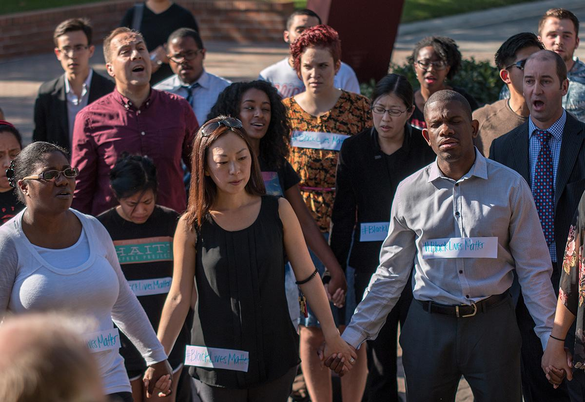 Students and faculty hold hands and sing Amazing Grace at the prayer vigil. | Aaron Fooks/THE CHIMES