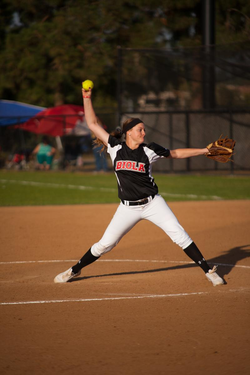 Junior Kendall Maddox winds up her pitch at the softball game against La Sierra University on Feb. 6.   Melanie Kim/THE CHIMES [file photo]