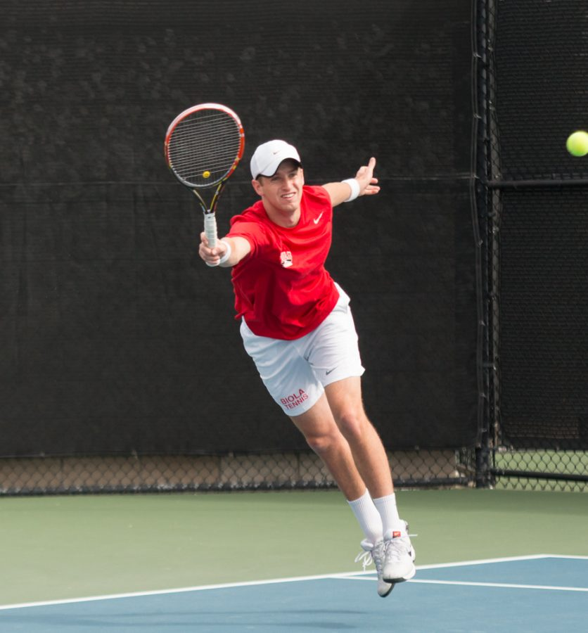 Sophomore Luke Mountain jumps up for the ball to strike during the tennis match this weekend. | Aaron Fooks/THE CHIMES [file photo]
