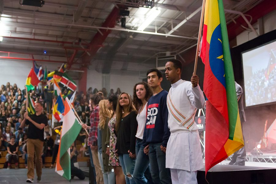 The SMU team India stands together between the flags of India and Ethiopia to honor the memory of their beloved team member and friend, Hasiet Joy Negash. The parade of nations demonstrates diversity with a representation of flags from various countries. | Kalli Thommen/THE CHIMES