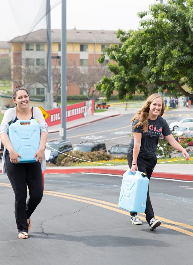 Amy McKeever, freshman communication disorders major and Stefanie Van Schooten, business administration freshman carry water jugs in order to spread awareness about the water crisis in Africa. Speakers, students and organizations communicate about missions and spreading the Gospel. | Molli Kaptein/THE CHIMES