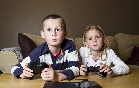 Siblings playing Video Games sitting in the sofa