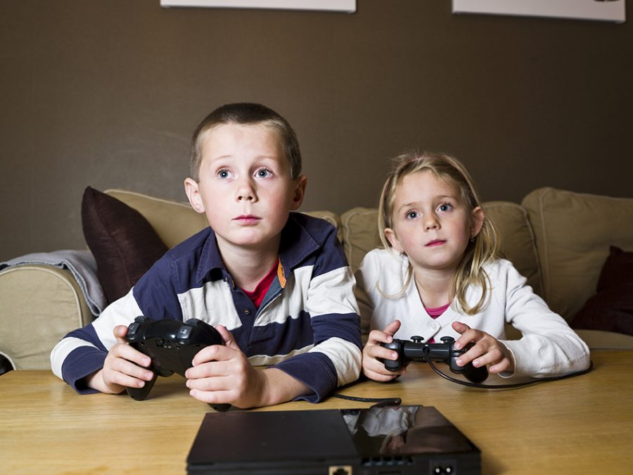 Siblings+playing+Video+Games+sitting+in+the+sofa
