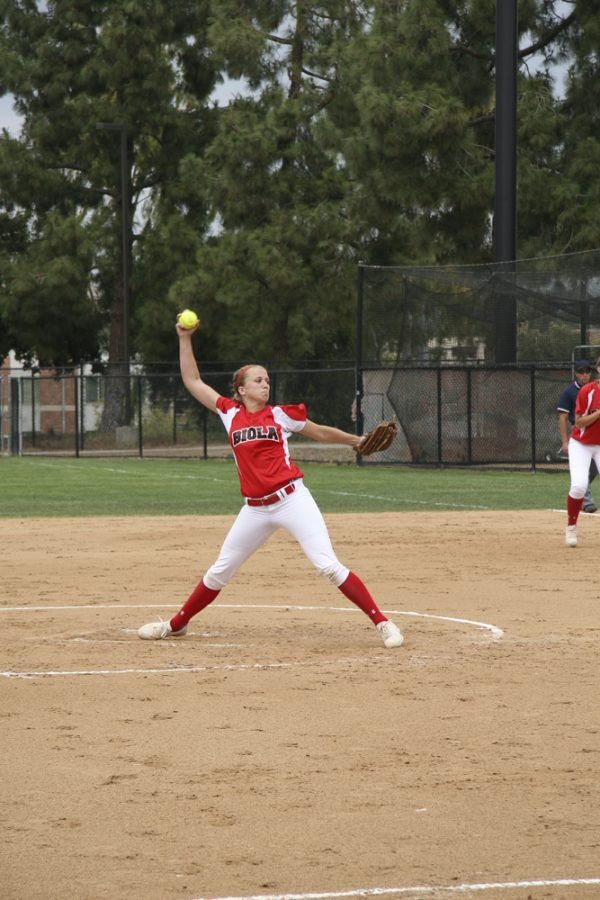 Sophomore right-handed pitcher Kimmy Triolo prepares a pitch against Concordia University on April 21.   Melissa Osswald/THE CHIMES [file photo]