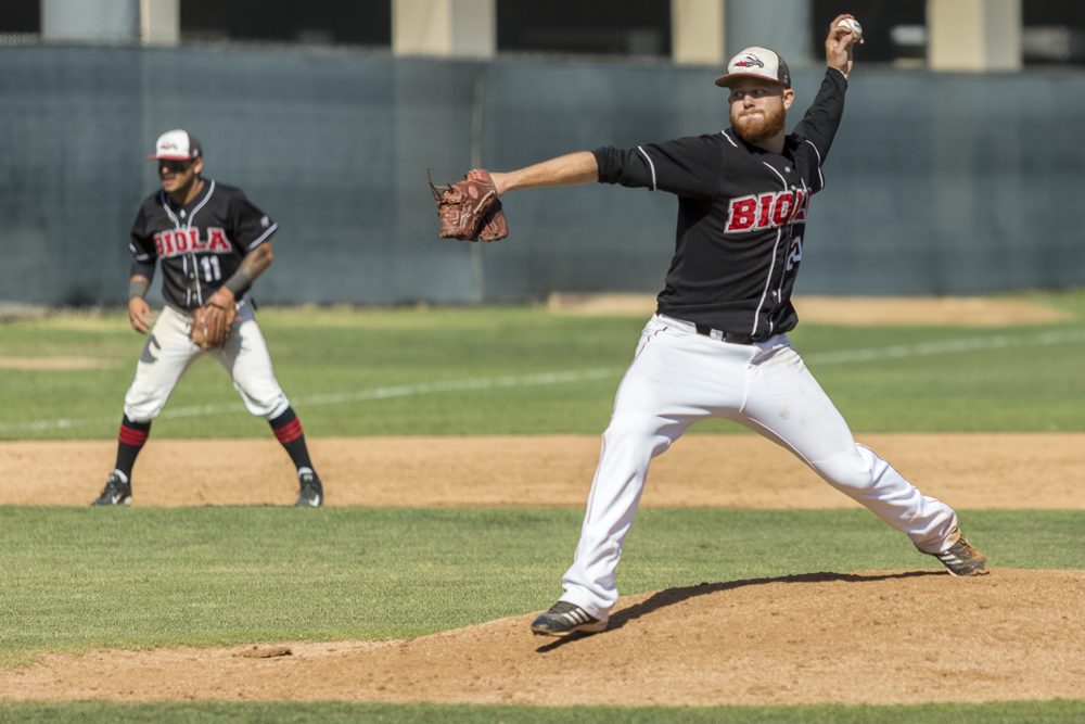 Senior pitcher Garrett Picha winds up the ball to pitch during the game last weekend. | Cherri Yoon/THE CHIMES [file photo]