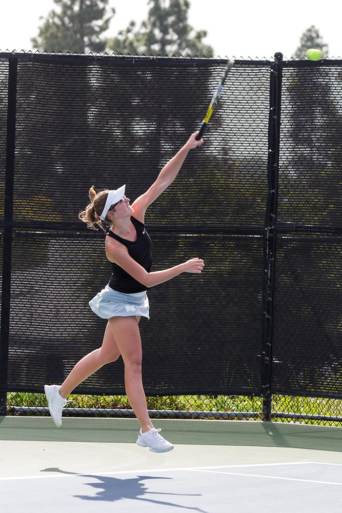 Sophomore Kelsey Post hits a hard serve against Principa College on March 10. Both men's and women's tennis teams will complete their seasons in Ojai this week. | Amber Nunn/THE CHIMES [file photo]