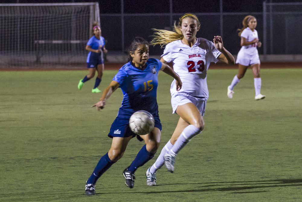 Junior Taylor Venegas pushes her way towards the ball in the heat of Biola's home game last week. | Matthew Matiz/THE CHIMES