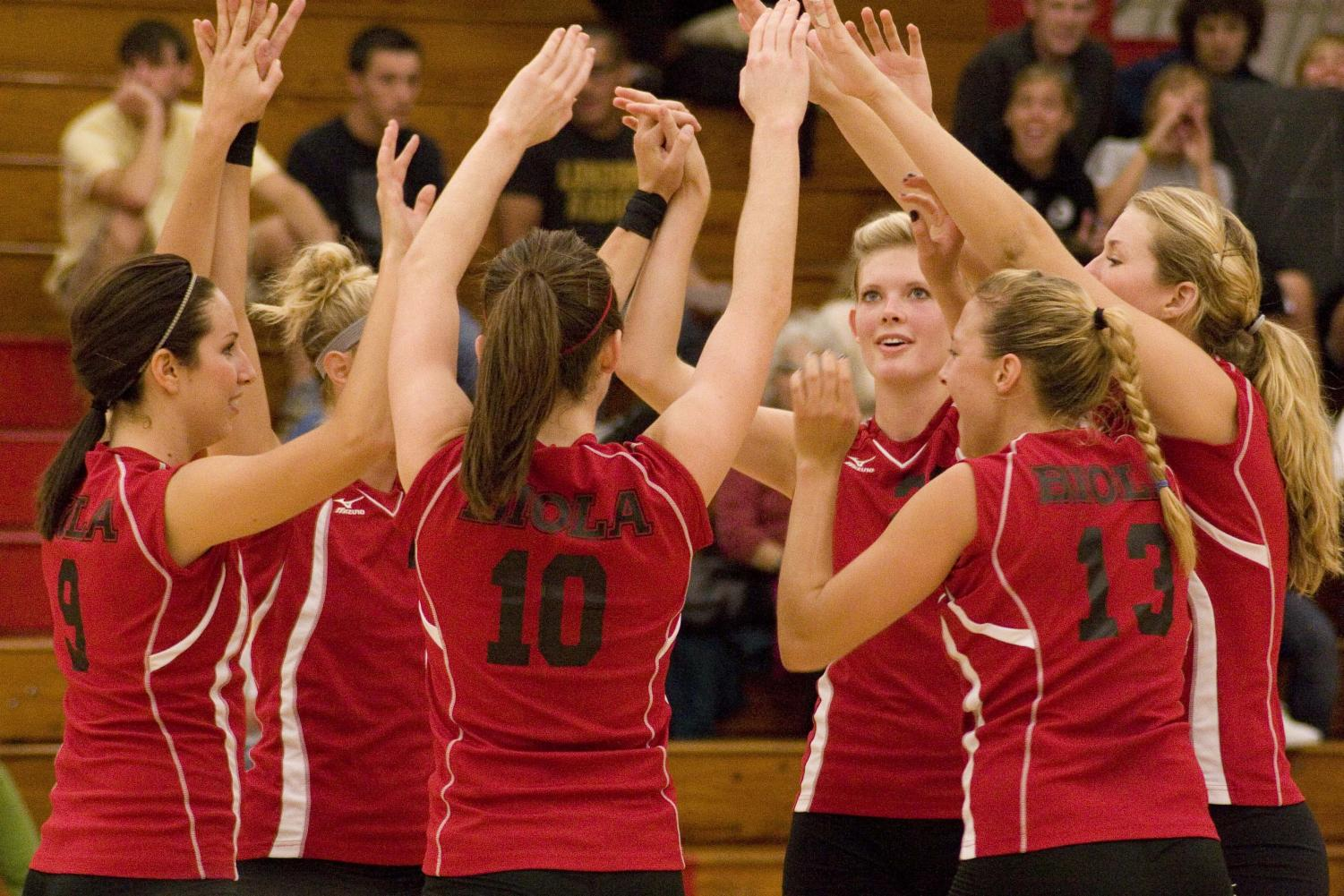 The volleyball team celebrates with some high fives during their victory over Westmont Tuesday night's game.