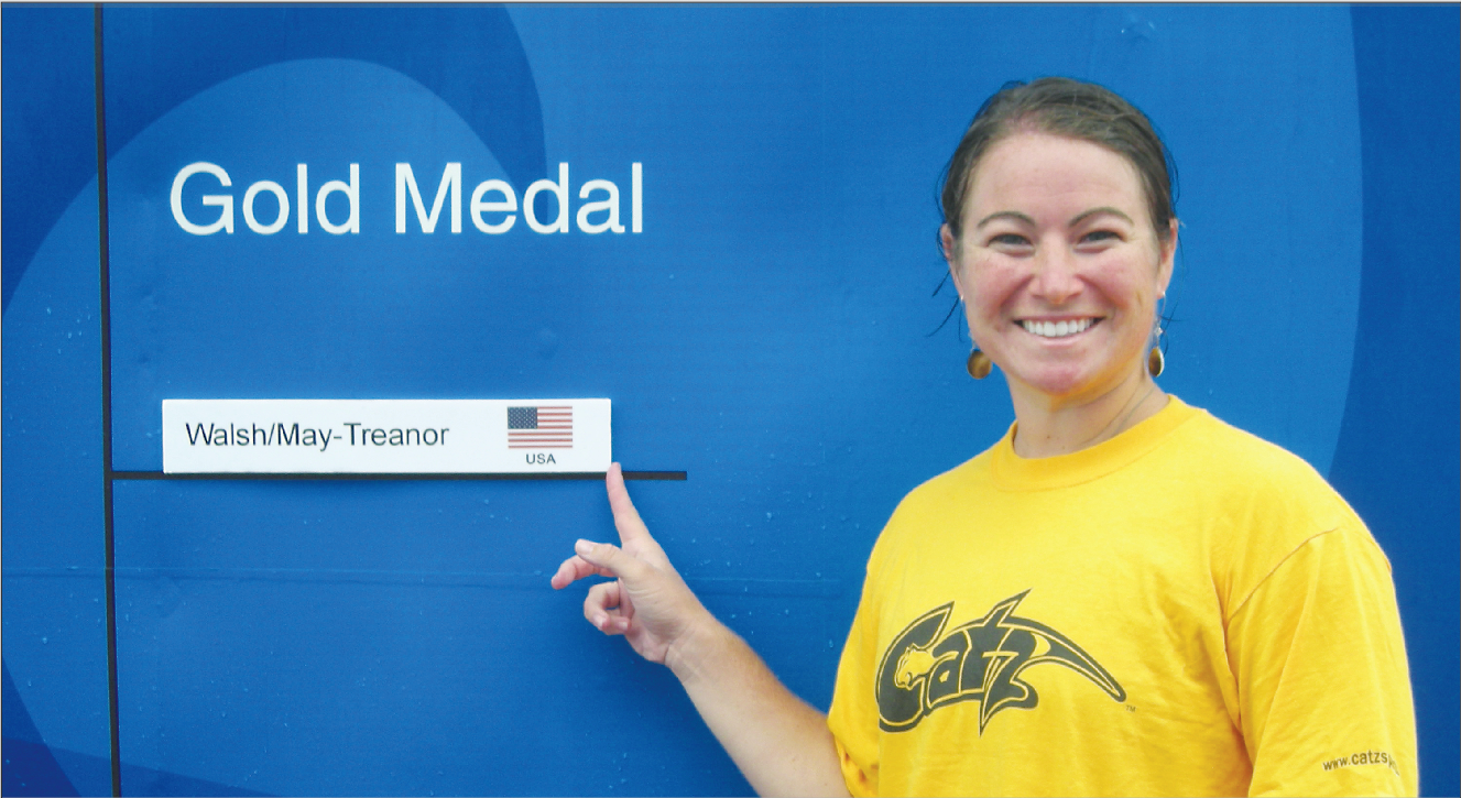 Anya Tronson poses for a picture next to the final gold medal bracket, showing the winners of the women's beach volleyball event.