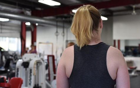A student wearing a tank top in the fitness center.