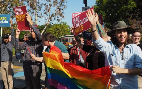 Demonstrators in front of Biola's entrance wave to passing cars while holding signs in support of LGBTQ individuals.