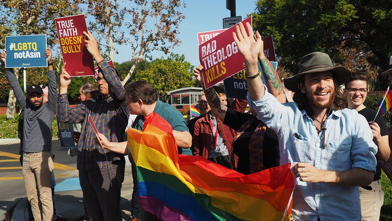 Demonstrators+in+front+of+Biola%27s+entrance+wave+to+passing+cars+while+holding+signs+in+support+of+LGBTQ+individuals.