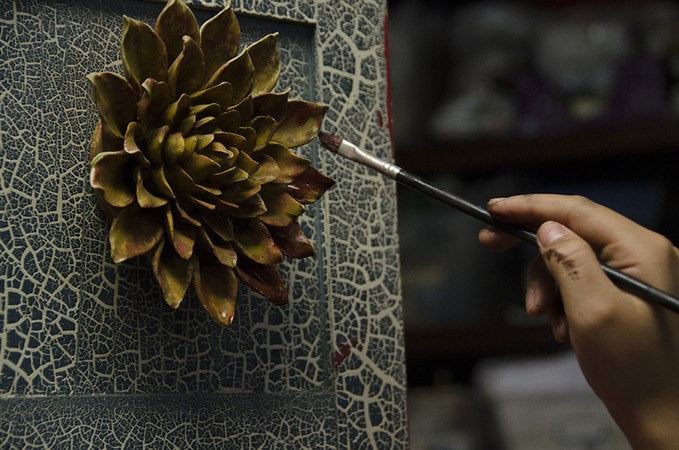 A hand painting a flower